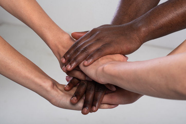 shot of mixed race three people holding hands together.
